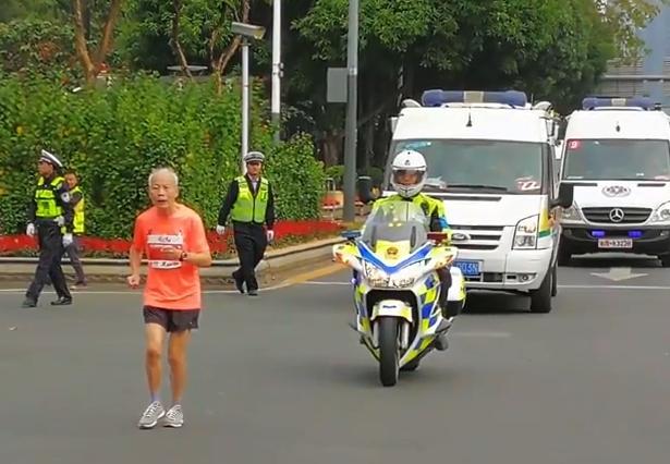 80歲深馬選手6.5小時跑完全程,一路陪護的交警在終點為他重新拉起衝刺帶